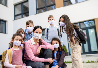 group-of-children-teacher-with-face-masks-outdoors-VRH2JGD
